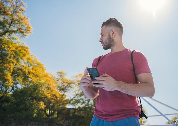 トレーニング前に彼の携帯電話をチェックしている若い男のローアングルショット