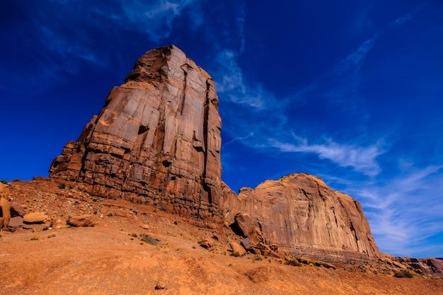 背景の青い空と大きな砂漠の岩のローアングルショット