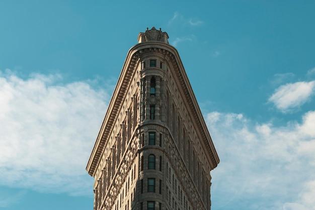 Низкий угол снимка флэтайрон-билдинг в парке мэдисон-сквер в нью-йорке, сша