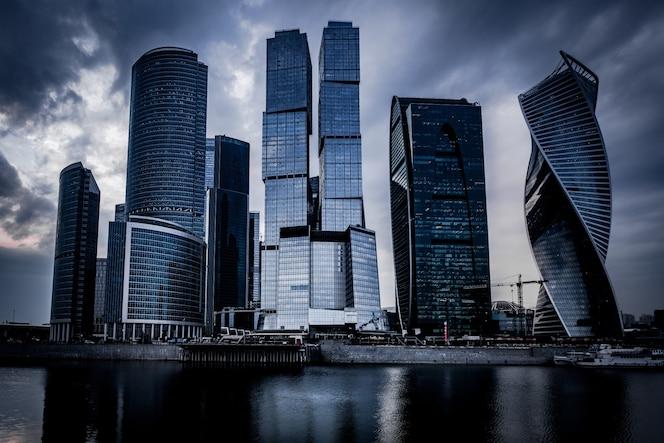 暗い曇り空の下で川の前にある灰色の高層ビルのローアングルショット