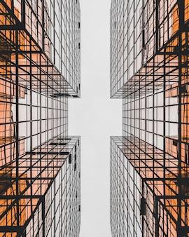 モダンな幾何学的なガラスの建物のローアングル ショットでクロス ビューを作る、香港