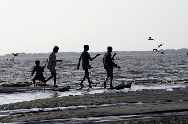 해변에서 걷는 사람들의 낮은 각도 샷
