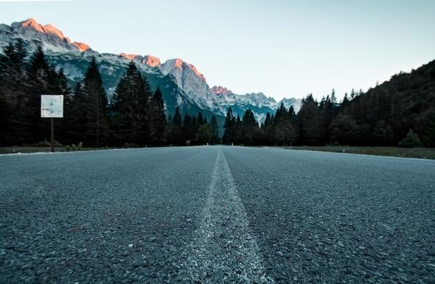 Низкий угол обзора дороги в лесу с горами на расстоянии в национальном парке долины вальбона, албании
