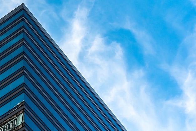 曇った青い空の下で背の高いガラスの建物のローアングルショット
