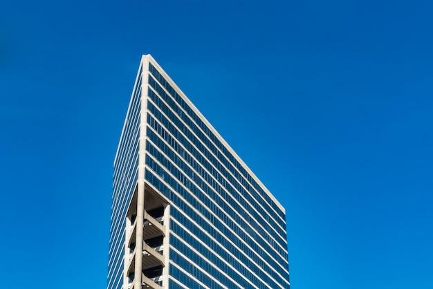 흐린 푸른 하늘 아래 높은 유리 건물의 낮은 각도 샷