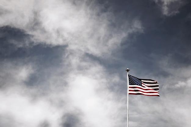 흐린 하늘 아래 기둥에 있는 미국 국기의 낮은 각도 샷