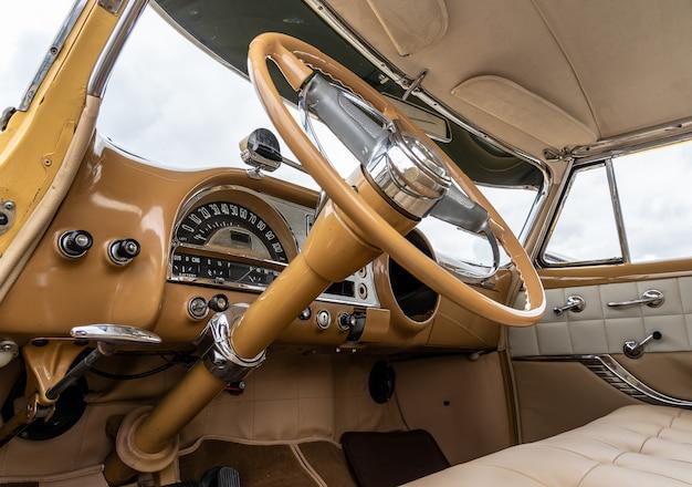 Снимок салона автомобиля под низким углом, включая рулевое колесо.
