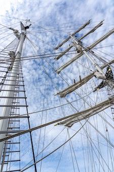 曇り空の下での大型帆船のマスト、索具、ロープのローアングルショット