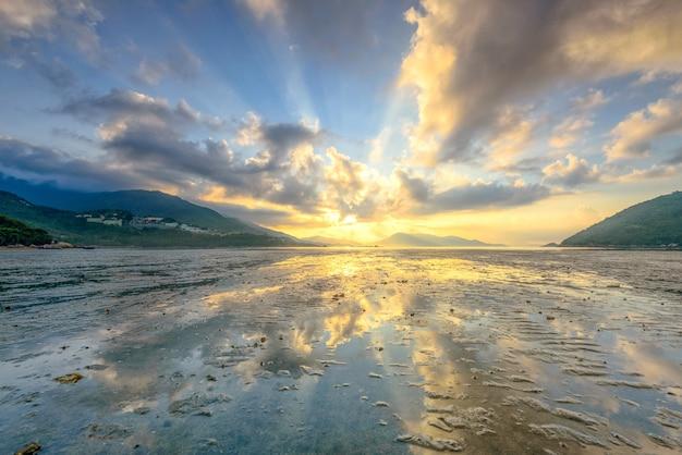 青い空の息を呑むような光と雲の下での海のローアングルショット