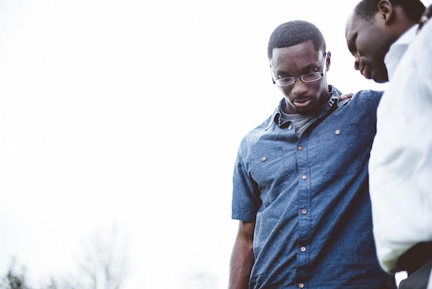 두 명의 아프리카 계 미국인 친구가 아래를 내려다 보면서 닫힌 눈으로기도하는 낮은 각도 샷