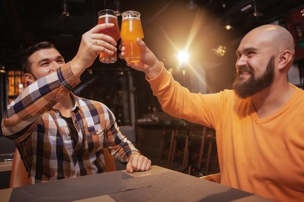 2人の男性の友人がビールパブで祝って、グラスをチャリンというローアングルショット