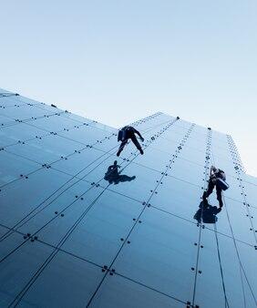 高層ビルの横で懸垂下降する2人のローアングルショット