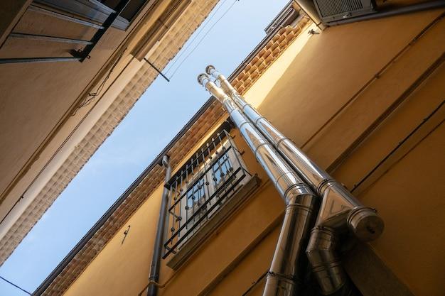 窓の隣の建物を上る2本のパイプのローアングルショット