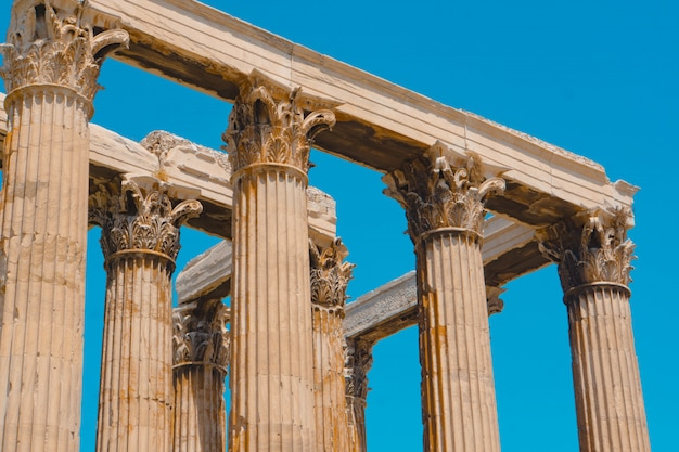 Low angle shot of old greek stone pillars with a clear blue sky