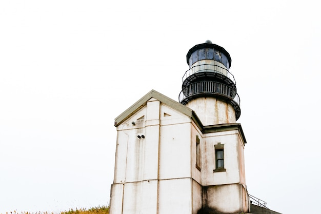 Low angle shot of an old lighthouse with a white sky