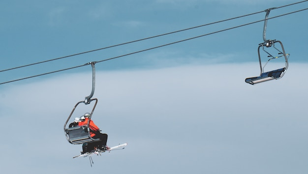 Low angle shot of people on a ropeway under the beautiful blue sky