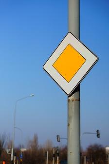 Inquadratura dal basso di un cartello stradale prioritario sotto un cielo blu chiaro