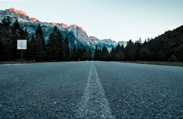 Low angle shot of road in forest with mountains in distance in valbona valley national park albania