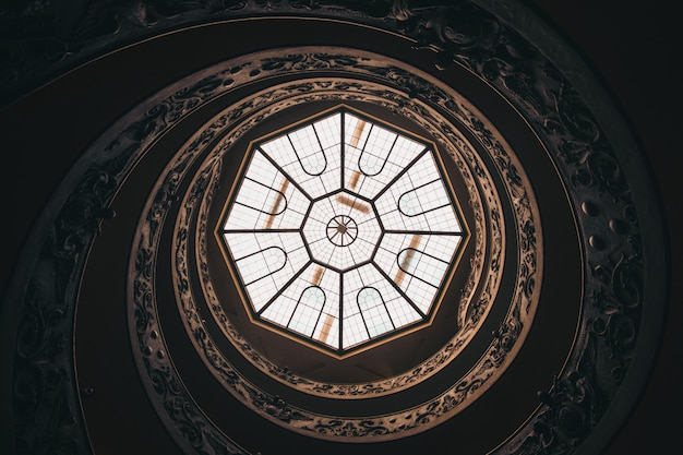 Low angle shot of a round ceiling with a window in a museum in vatican during daytime