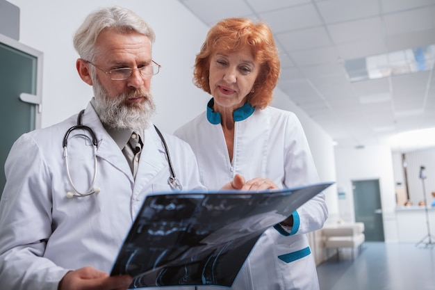 Low angle shot of a senior male doctor and his female colleague examining mri scan of a patient