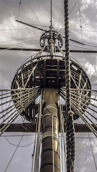 Low angle shot of a ship's main mast under the cloudy sky