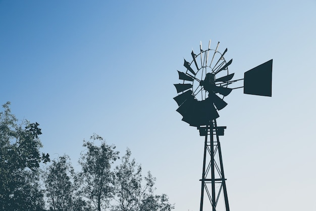Low angle shot of the silhouette of a windmill over the trees
