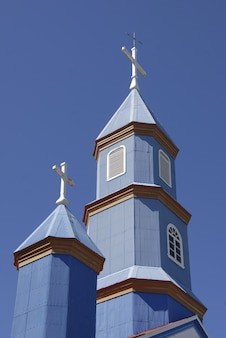 Low angle shot of a small blue church under a blue and clear sky