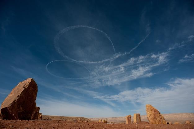 Inquadratura dal basso di tracce bianche a spirale nel cielo nel deserto