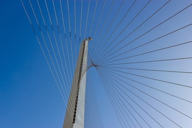 Low angle shot of steel cables with a clear blue sky