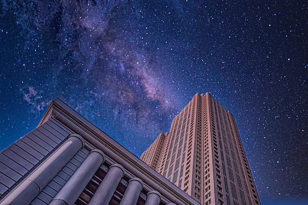 Inquadratura dal basso di edifici alti sotto un cielo notturno stellato