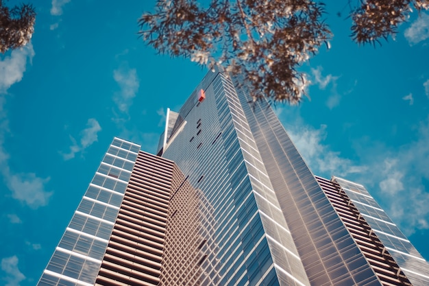 Low angle shot of a tall business building with a blue cloudy sky