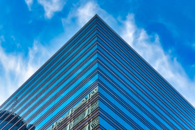 Low angle shot of a tall glass building under a blue cloudy sky
