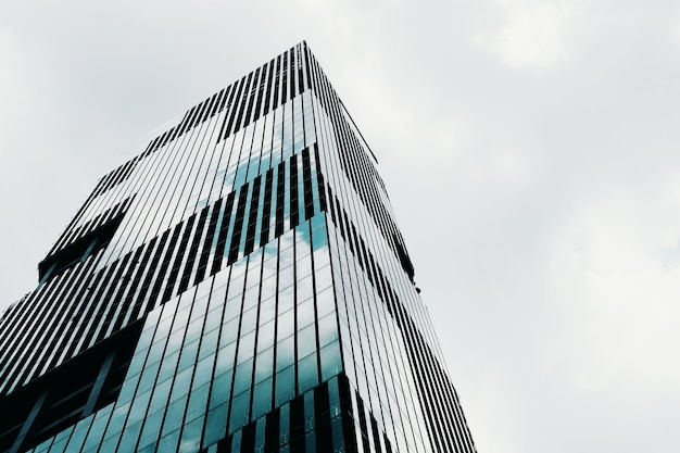 Low angle shot of a tall high-rise modern business building with a clear sky