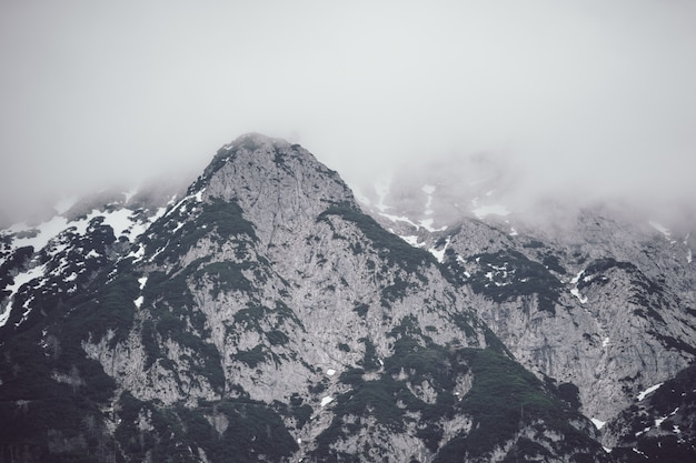 Low angle shot of a tall rocky mountain covered with thick fog