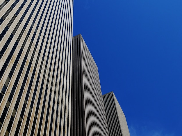 Low angle shot of three identical skyscrapers under the bright blue sky