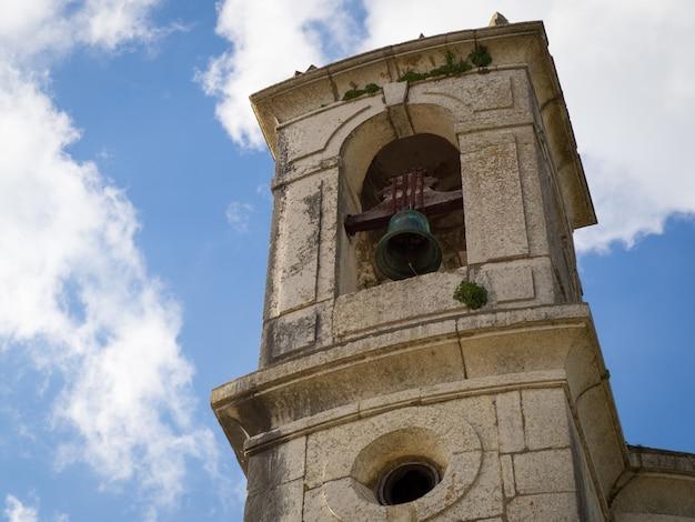 Inquadratura dal basso di una torre con una campana nera e un cielo nuvoloso
