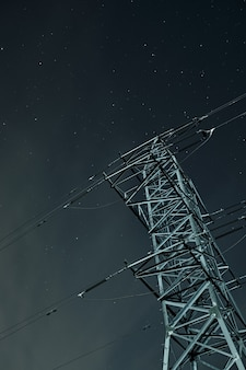 Low angle shot of a transmission tower under a starry sky