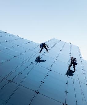 Inquadratura dal basso di due persone che si calano in corda doppia sul lato di un edificio alto