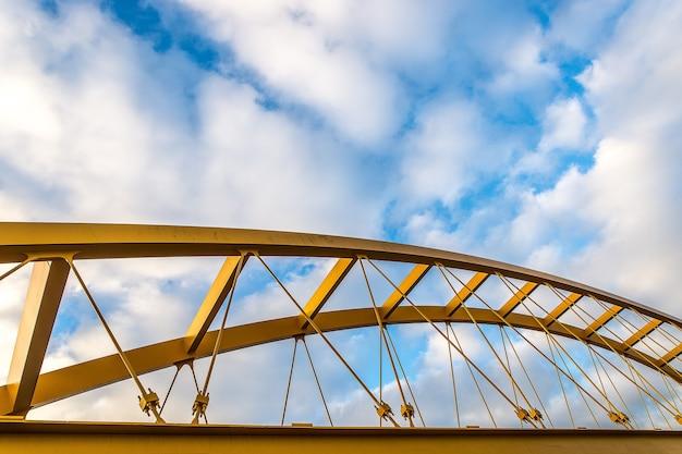 Inquadratura dal basso di un ponte strallato giallo con un cielo nuvoloso blu