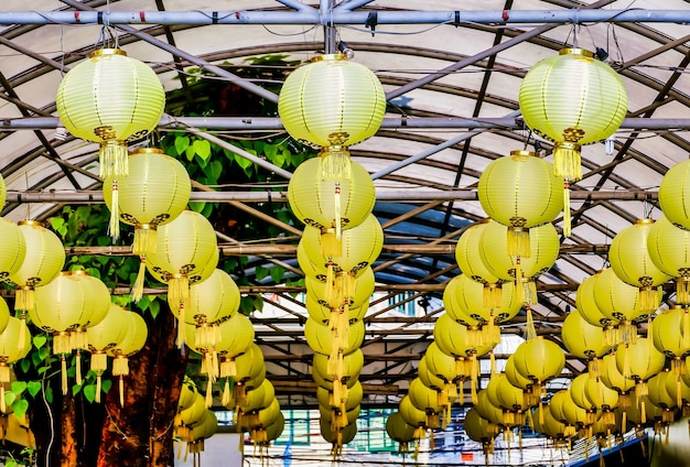 Low angle shot of yellow paper lanterns hung from the metal bars of a ceiling captured in laos