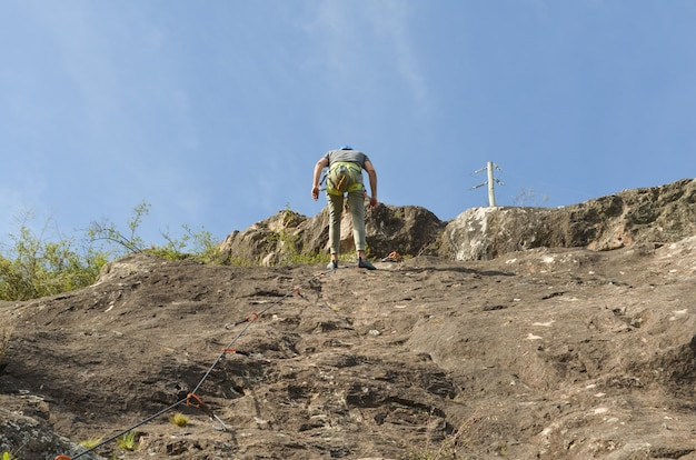 Low angle shot of a young hiker climbing up mountains