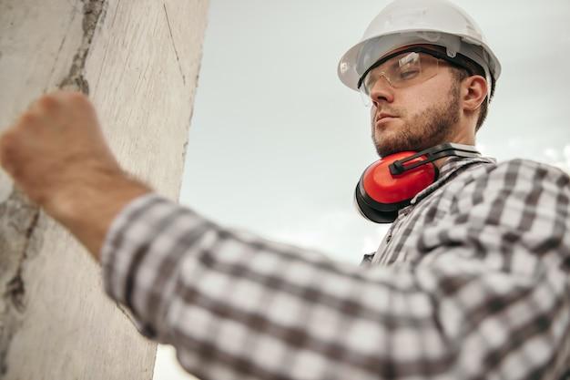 Вид сбоку под низким углом опытного мужчины-строителя в каске и защитных очках с наушниками на шее, работающего возле бетонной колонны на строительной площадке