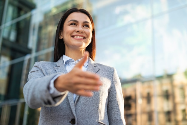 Low angle of smiley businesswoman giving hand for handshake outdoors