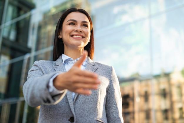 Basso angolo di smiley imprenditrice che dà la mano per la stretta di mano all'aperto