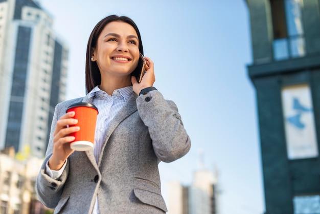 Basso angolo di smiley imprenditrice parlando al telefono mentre beve il caffè