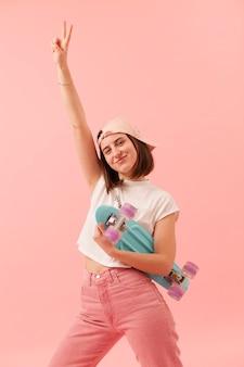 Ragazza di smiley di angolo basso con skateboard