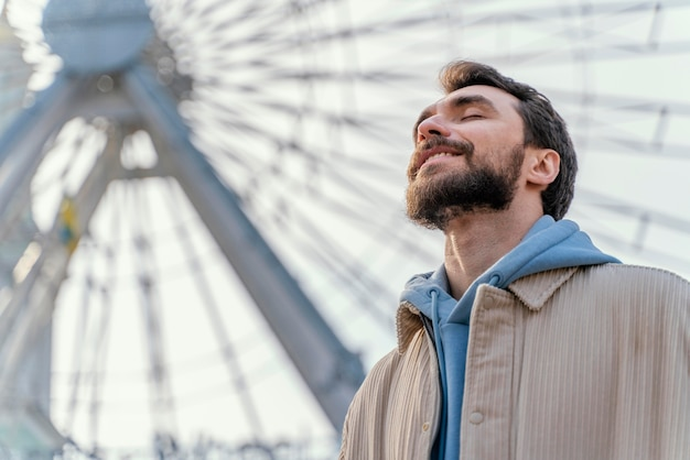 Low angle of smiley man outdoors next to ferry wheel