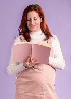 Low angle smiley pregnant woman reading book
