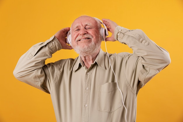 Low angle smiley senior listening music