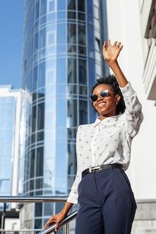 Low angle smiley woman waving